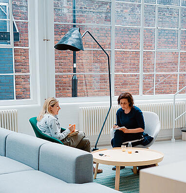 Two women sit in the lounge area of a historic building, discussing something and taking notes.